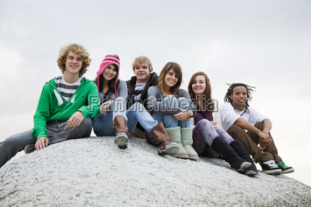 group of friends sitting on boulder