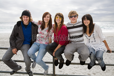 group of friends sitting on railings