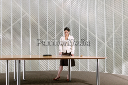 businesswoman standing by table