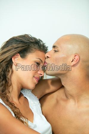 man kissing girlfriends forehead