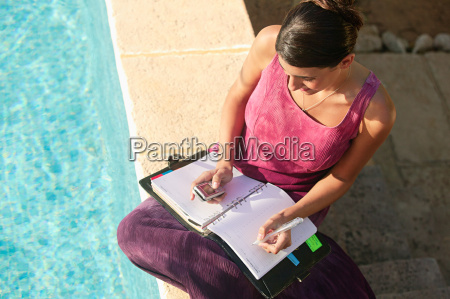 woman by swimming pool with cellphone