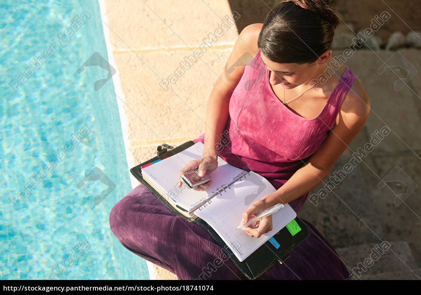 woman, by, swimming, pool, with, cellphone - 18741074
