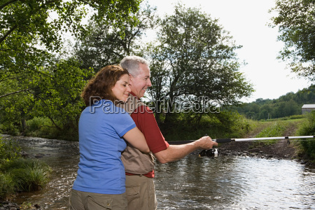 mature couple fishing in stream