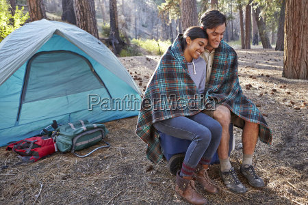 young camping couple wrapped in blanket