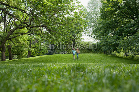 teenage couple walking in a park