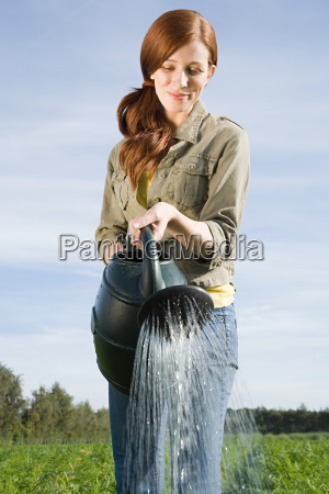 young woman watering plants in field