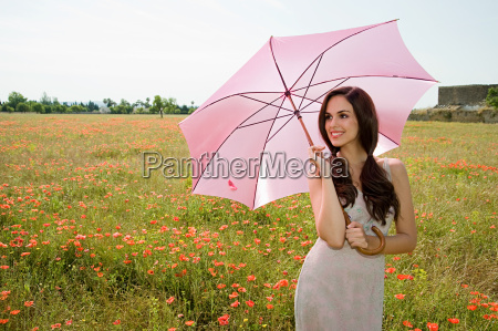 young woman in poppy field with
