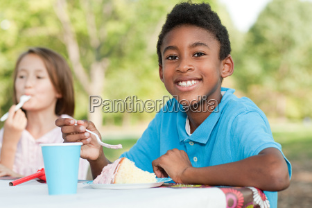 boy at birthday party eating birthday