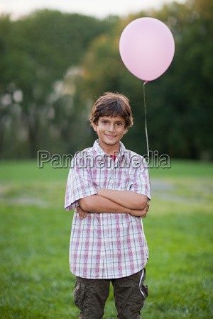 boy at birthday party holding pink
