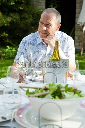 senior man having lunch with wine