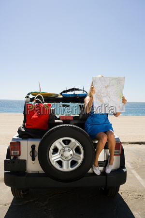 young woman sitting on vehicle looking
