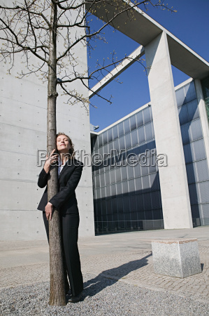businesswoman hugging a tree
