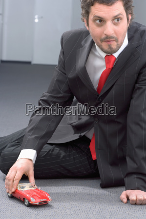 businessman playing with toy car