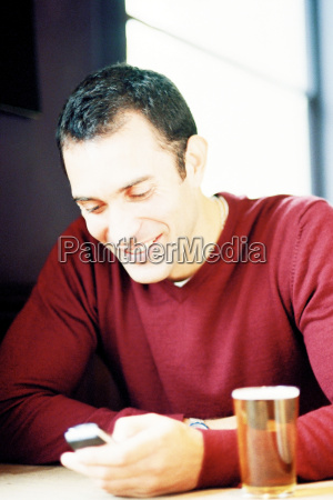 man with text messaging in pub