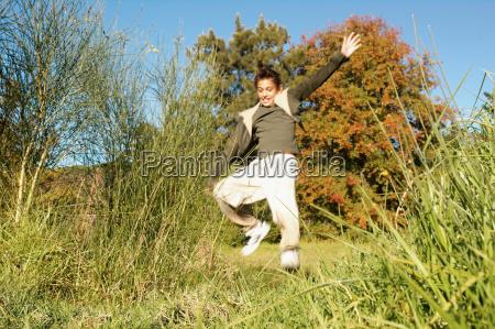 boy running in meadow