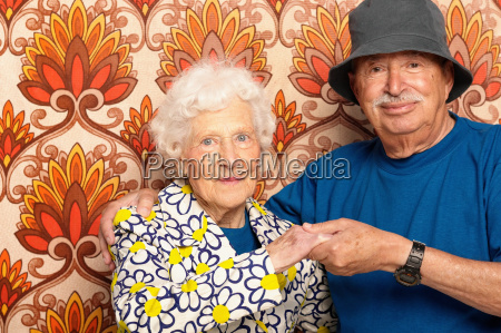 smiling elderly couple holding hands