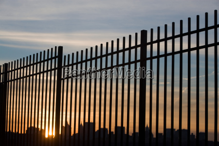 new york skyline through a fence