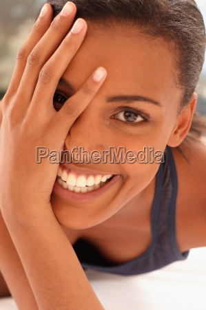 smiling young woman partially covering face