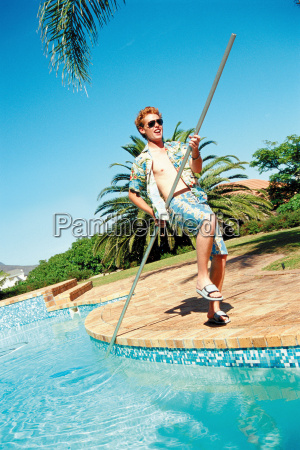 young man cleaning the pool