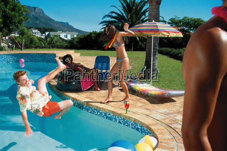 young man falling into pool