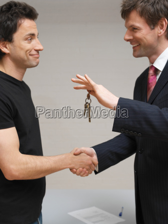 men shaking hands and exchanging keys