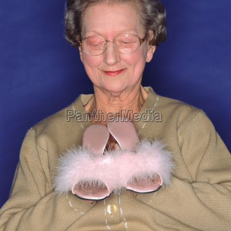 senior woman holding sexy slippers