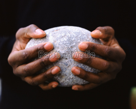 a man holding an oval stone