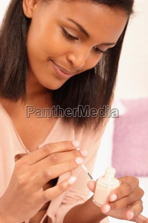smiling young woman with nail polish