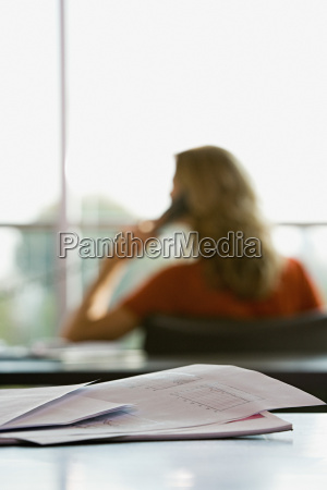 paperwork and woman on the telephone