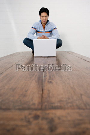 man with laptop sitting on table