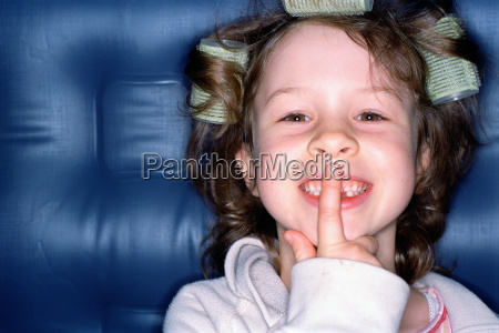 smiling girl with finger on lips