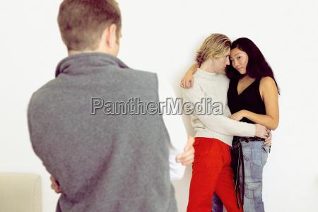 man watching couple hugging