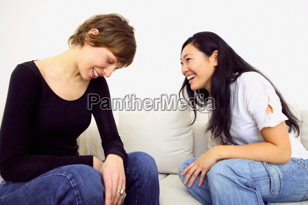 two women laughing on sofa