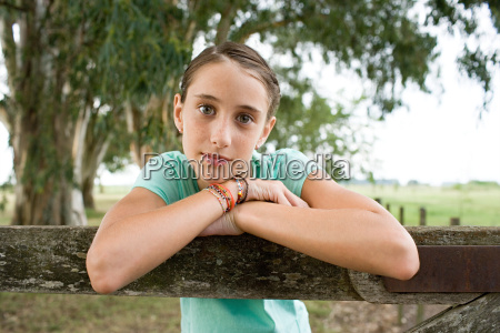 girl leaning on a wooden fence