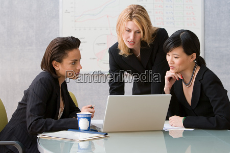 three young women looking at laptop