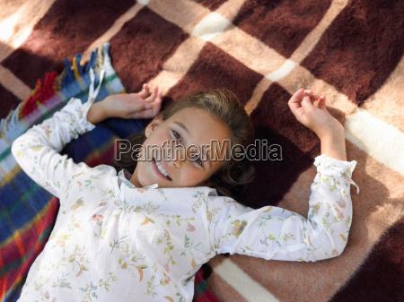 girl lying on blankets