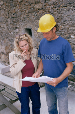 man and woman looking at plans