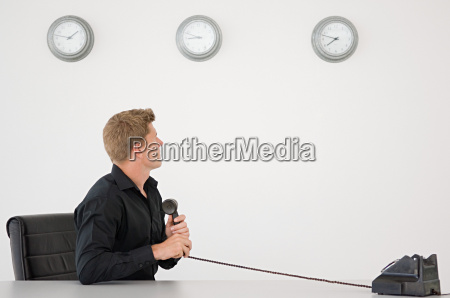 businessman watching the clock holding telephone
