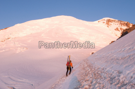 male climber carrying skis up mountain