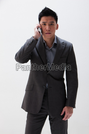 young asian businessman using cellphone studio