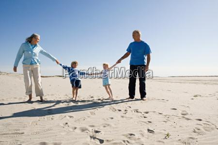 grandparents and grandchildren holding hands walking