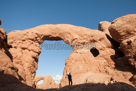 person standing under turret arch arches
