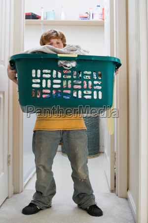 a boy carrying a laundry basket