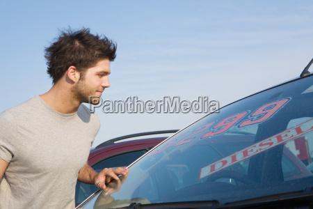 a man looking at a car