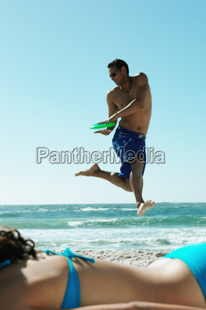 man playing with frisbee on beach