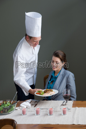 a chef serving a woman with