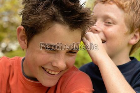 boy whispering to friend