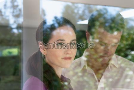 woman looking through window man looking