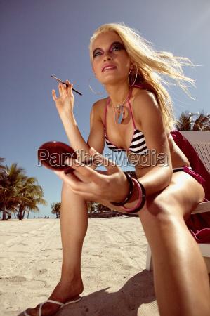 woman, applying, make, up, on, beach - 18781588