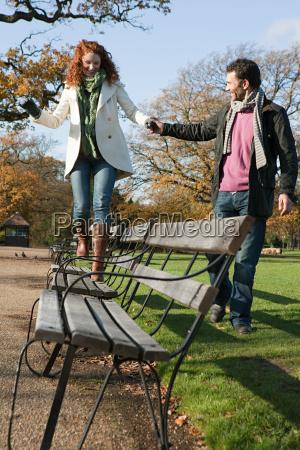 a woman walking across a park